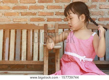 cute or adorable asian children catch pigtail and wearing pink or red dress sit for relax on the old or vintage wood chair on street and brick wall background