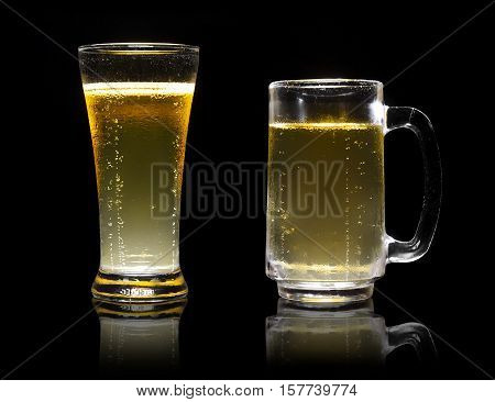 dual or two frosty lager light beer in clear glass set with steam for winter drink or celebration isolated on black background and beer glass reflection