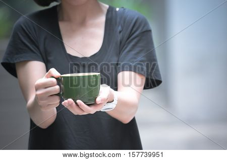 Female hands holding cups of coffee, concept about giving