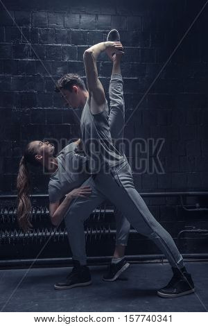 Twine. Involved flexible young dancer making a twine while performing together with another dancer in the dark lighted room and expressing concentration and confidence