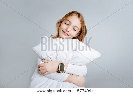 Sweet dreams. Pleasant cute little girl holdign white pillow and embracing it while going to sleep