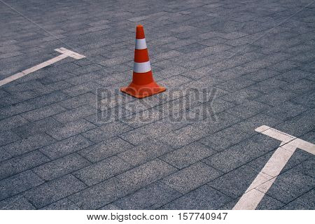 Closed car parking lot with white mark and orange traffic cone on street