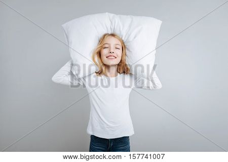 Full of delight. Pleasant content litle girl closing her eyes and holdign her head on the pillow while resting
