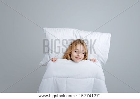 Real emotions. Pleasant nice little girl lying in bed and closing her eyes while pretending to sleep