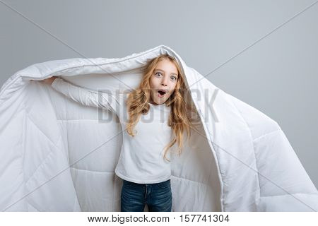 Like a ghost. Pleasant emotional little girl covering with blanket and expressing positivity while standing isolated on grey background