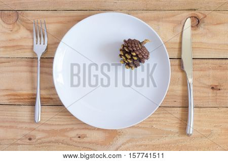 christmas dinner table : pine cone in white dish and fork knife on wood table