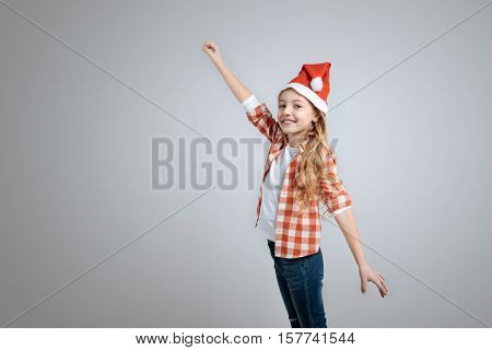 Share sincere emotions. Positive little nice girl holding hand up and expressing gladness while standing isolated on grey background
