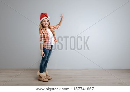 My little toy. Cheerful cute smiling girl ringing the bell and looking at you while celebrating New Year
