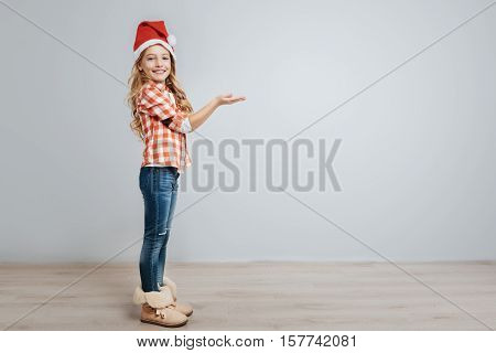 Happiness in mind. Cheerful delighted little girl catching snowflakes and smiling while celebrating Christmas