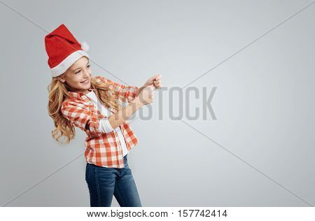 Make a little party. Positive content cute little girl smiling and holding flapper while standing isolated on grey background