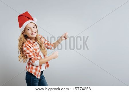 True emotions. Positive delighted little girl smiling and celebrating Christmas while standing isolated on grey background
