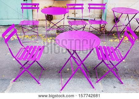 picturesque scene with vintage pink table and chairs in Paris