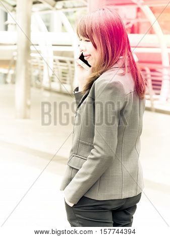 Soft focus of Young beautiful girl calling by phone in transit station