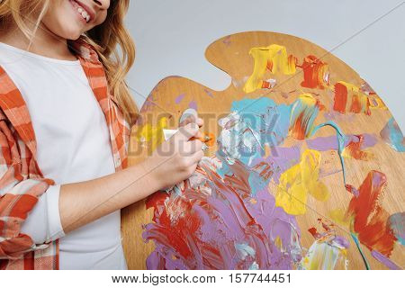 Brighten your life. Close up of palette in hands of little cute girl holdign it and smiling while being involved in painting