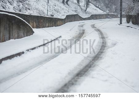 Road with snow falling asleep. Winter time. Heavy snowfall. Beautiful landscape. The trunks and branches of trees.