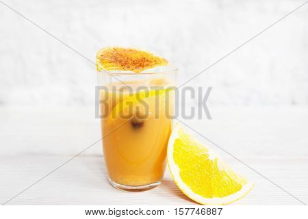 Fresh orange juice in glass on white background. Portion of citrus fresh with orange slice and spices, free space for text. Refreshment, cocktail, vitamins concept