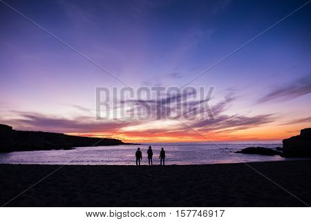 Silhouette of three friends standing on the sandy ocean beach at sunrise