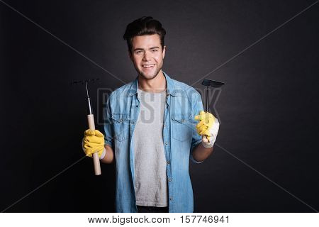 Garden utensils. Cheerful content smiling gardener holding shovel and garden equipment whle enjoying gardening on black background