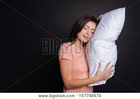 Rest after hard day. Positive content beautiful woman holdign pillow and sleeping while standing isolated on black background