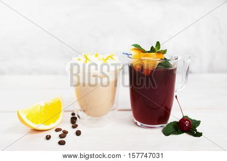 Latte and sangria glasses on white background. Two cups of coffee and punch with slice of orange, free space for advertisement or text. Refreshment, drink, party concept