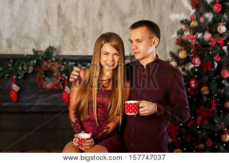 Loving couple and Christmas. Man and woman drinking from mugs Hot Christmas drink. Cocoa with marshmallows.