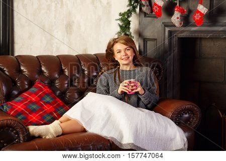 Cute attractive girl drinking hot Christmas drink cocoa with marshmallows. She's on the couch. Warm Christmas evening.