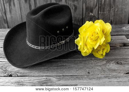 black cowboy hat with a yellow rose