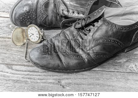black mens shoes with an old timepiece