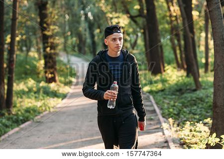 Handsome young man walking with plastic bottle. Attractive guy going in forest. Evening relaxation, tourism, hiking concept