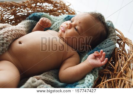 African newborn kid lying in wicker cradle close-up. Adorable child rest in nest. Naked innocent baby picture