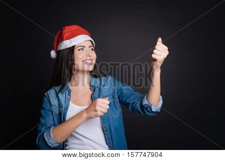 Make little party. Delighted smiling charmign woman using flapper ans expressing gladness while celebrating New Year