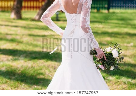 Unrecognizable bride hurry to groom, outdoor. Woman in beautiful wedding dress walking on green grass with wedding bouquet in hand. Happiness, love, dream concept