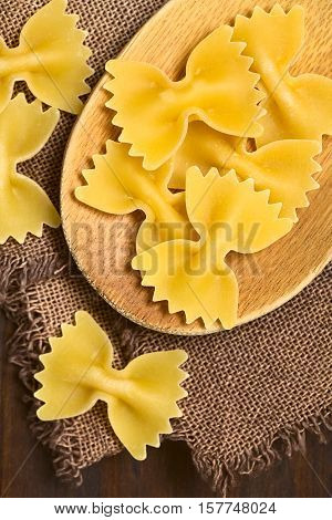 Raw farfalle or bow-tie pasta on wooden spoon photographed overhead with natural light (Selective Focus Focus on the pasta on the spoon)
