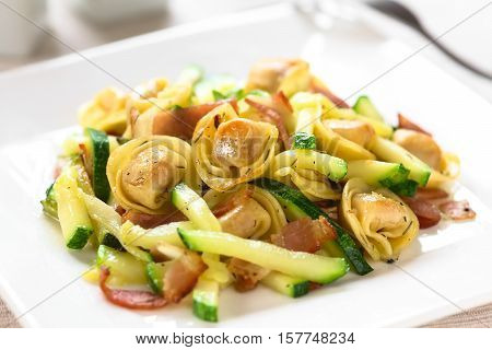 Baked cheese tortellini or belly button pasta with zucchini bacon and thyme photographed with natural light (Selective Focus Focus on the tortellini on the top)