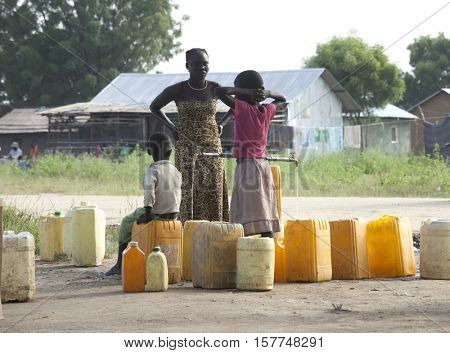 BOR, SOUTH SUDAN-OCTOBER 31, 2013: Unidentified people fill water containers at a filling point in South Sudan