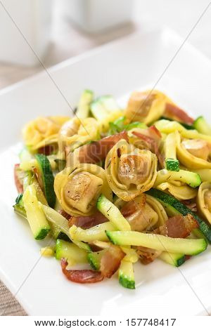 Baked cheese tortellini or belly button pasta with zucchini bacon and thyme photographed with natural light (Selective Focus Focus on the tortellinis on the top of the dish)