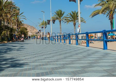 Alicante, Spain - September 9, 2016; Promenade along Postiguet Beach people walking in distance Alicante Spain street and building scene