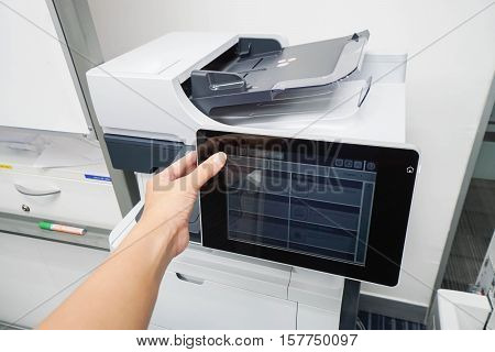 women press printer screen by left hand for scanning documents