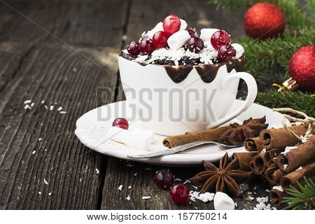 Mug cupcake New Year Christmas with marshmallow and juicy cranberries on a wooden background with toys and pine branches. Holiday breakfast