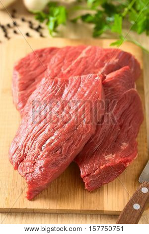 Fresh raw boneless beef meat cut in slices on wooden board photographed with natural light (Selective Focus Focus in the middle of the image)