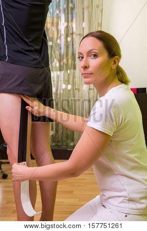 Female physiotherapist putting kinesio tape on patients leg