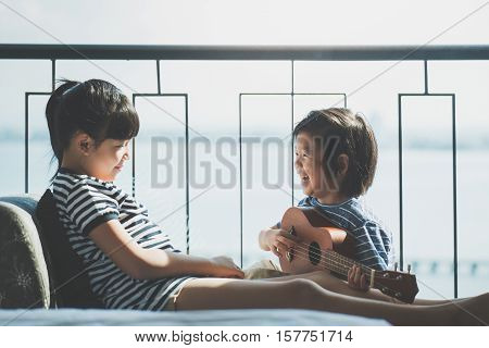 Asian chidren playing ukulele together near the window