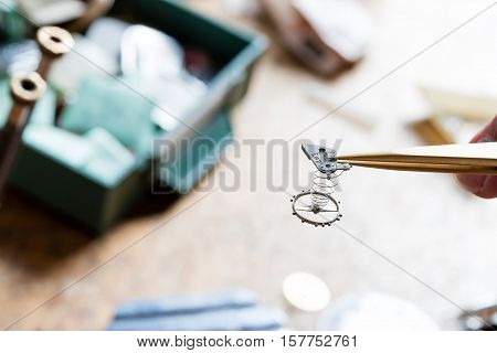 tweezers holding a clockwork on the foreground
