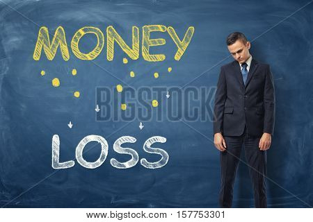 Sad businessman standing near the words 'money loss' written on dark blue wall. Business and management. Failures and problems. Poses and gesrures.