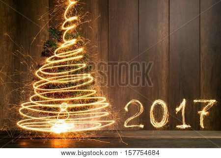 Abstract Symbolic Christmas Tree And 2017 Created Using Sparklers With Wood Table And Wood Wall Back