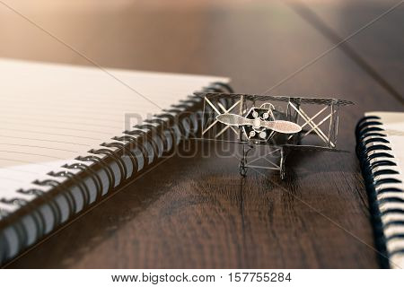 Vintage Model Plane On Wood Table With Notebook And Notepad Freedom Of Thought Concept Background.