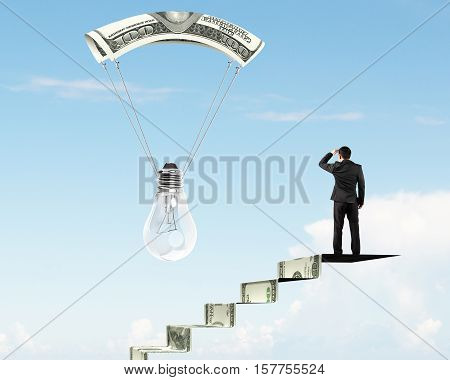 Man On Money Stairs Looking Light Bulb With Money Parachute