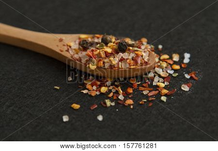 Spoon with different spices on the black background
