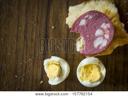Lean breakfast. Bitten sandwich with beef sausage and boiled eggs on a chopping board