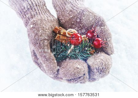Female hands in knitted mittens with nice Christmas firtree bouquet close up on light background with snowfall.  Winter and Christmas cozy concept.